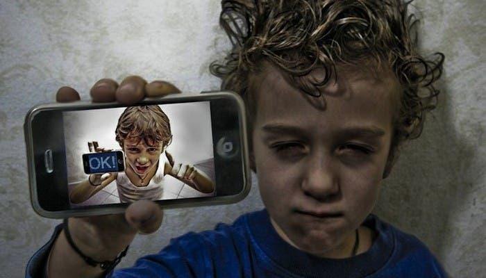 Un niño con un iPhone en la mano