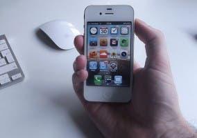 iPhone 4 blanco sujetado por una mano