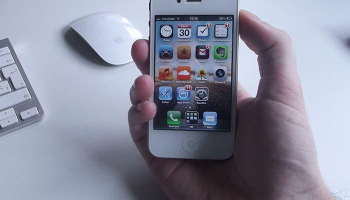 iPhone 4 blanco sujetado por una mano